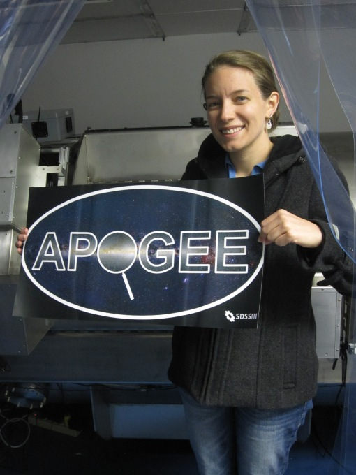 "Zasowski holding the APOGEE logo. The logo shows the word ""APOGEE"" inside a white ellipse, with the O as a magnifying glass on the Milky Way"
