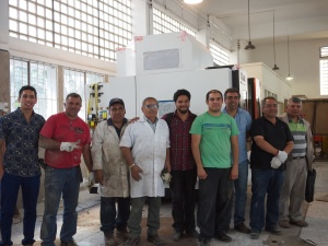 Happy Engineers standing in front of their just-delivered CNC machine. Ingenieros felices de pie frente a su recién entregada máquina CNC.